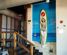 Retro painted surfboard and mural with pin up gidget girl