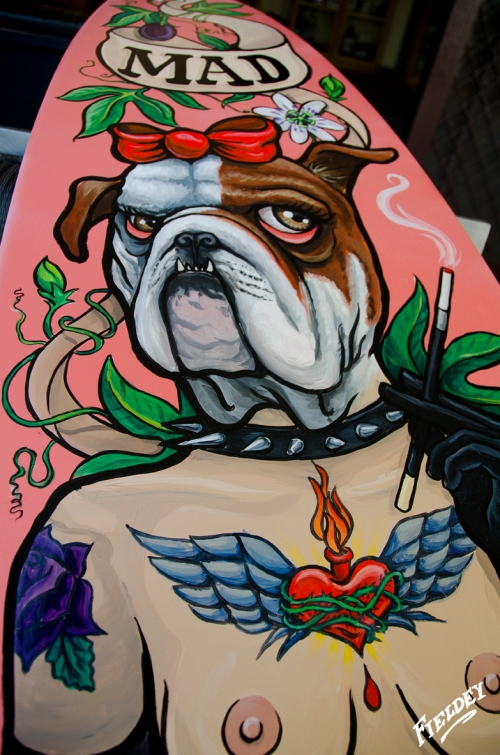 Painted surfboard with dog headed lady and tattoos