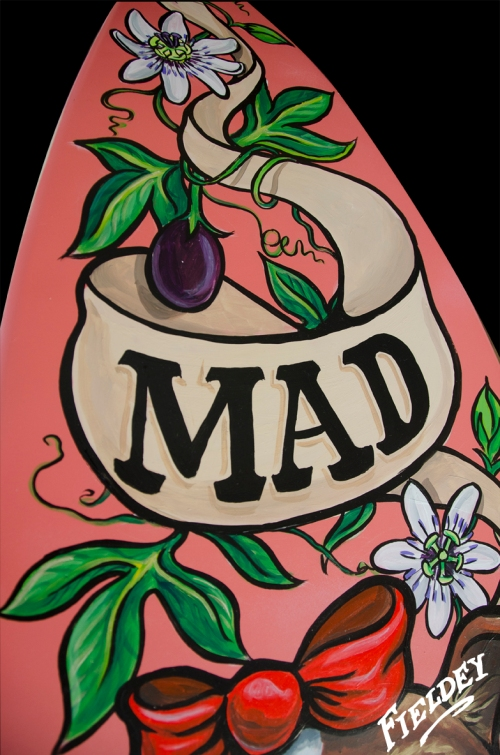 Painted surfboard showing old-school tattoo style banner and passionfruit