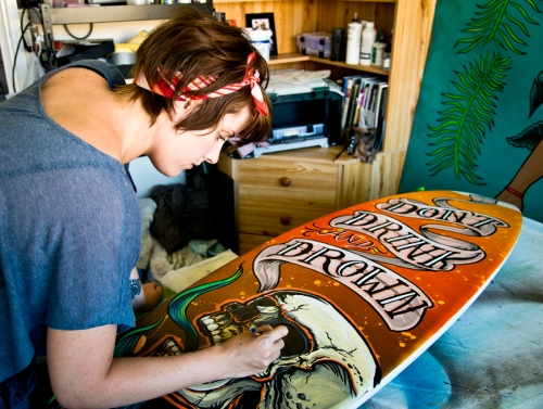 Fieldey painting a surfboard