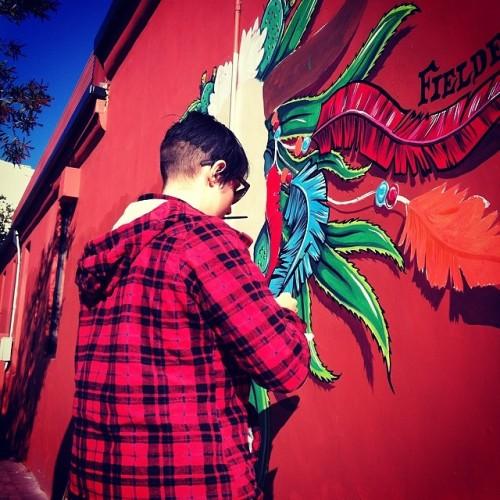 Fieldey painting a street art mural